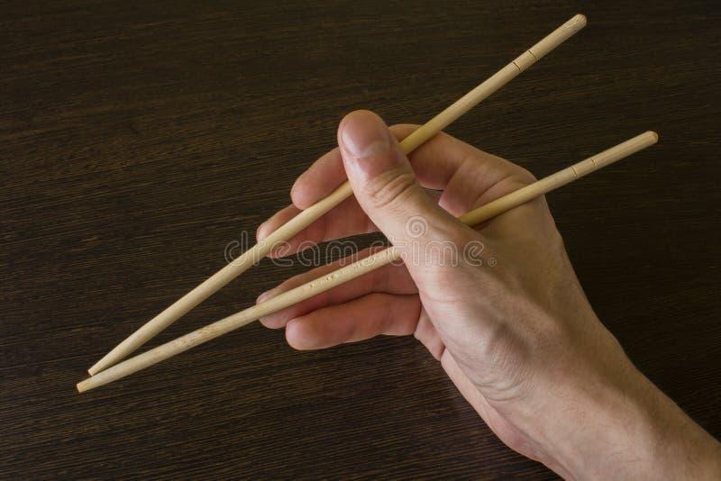 Палочки в правой руке на предпосылке древесины стоковые фотографии rf