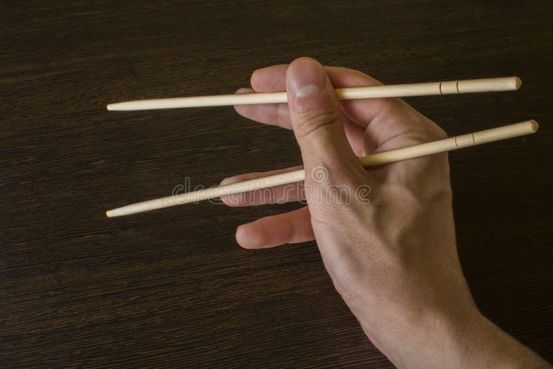 Палочки в правой руке на предпосылке древесины стоковое фото rf