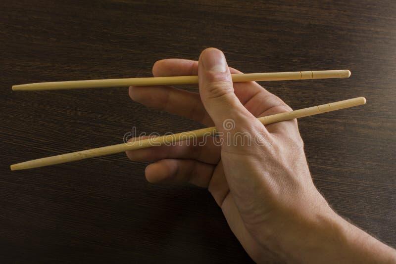 Палочки в правой руке на предпосылке древесины стоковое фото