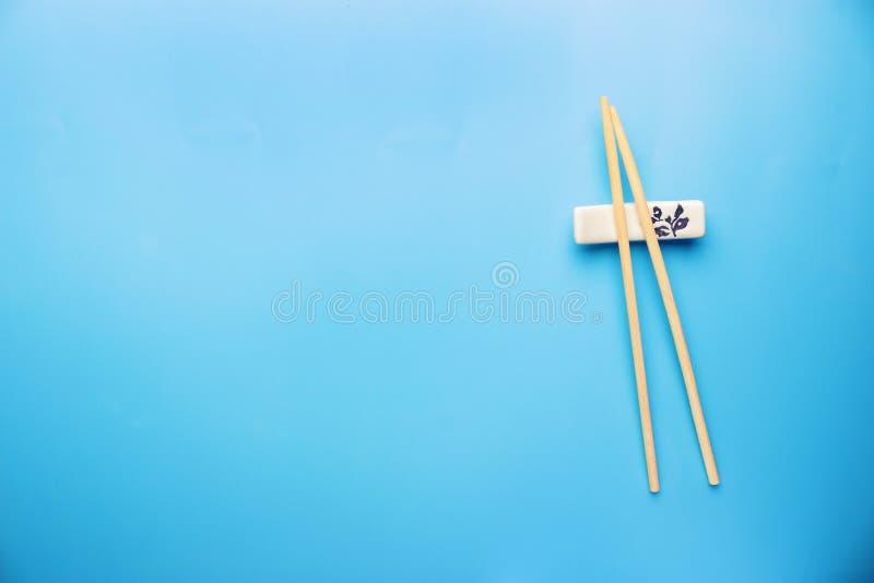 Палочки и соевый соус на голубой предпосылке стоковая фотография