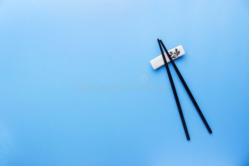 Палочки и соевый соус на голубой предпосылке стоковое фото