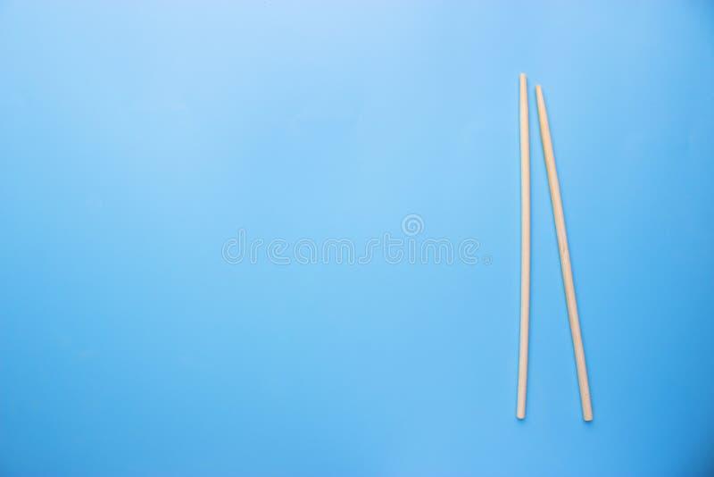 Палочки и соевый соус на голубой предпосылке стоковые изображения