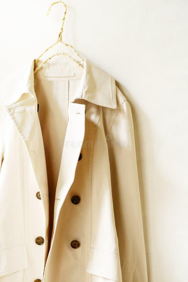 Пальто канавы бежа или greige элегантное изолированное над белизной стоковое фото