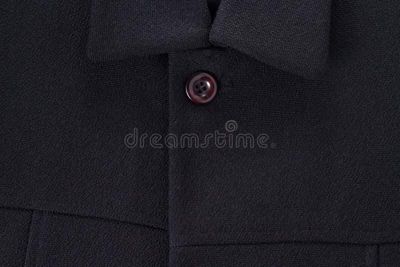 Пальто черноты конца-вверх с одной кнопкой на белой предпосылке с космосом экземпляра стоковое изображение