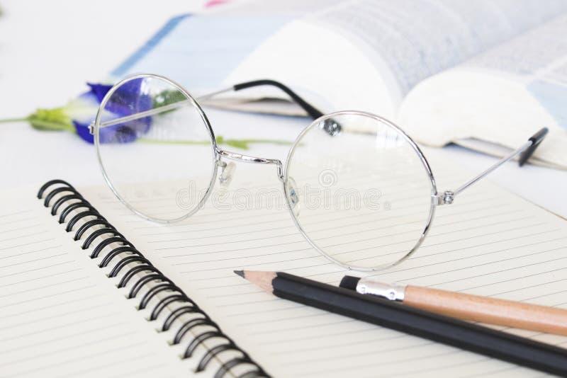 Памятка тетради, книга словаря и зрелище студента для исследования стоковые изображения rf