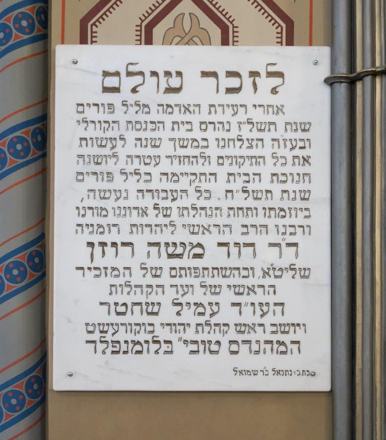 Памятная доска в памяти о восстановлении синагоги после землетрясения 1976 вися на стене синагоги Co стоковые фото