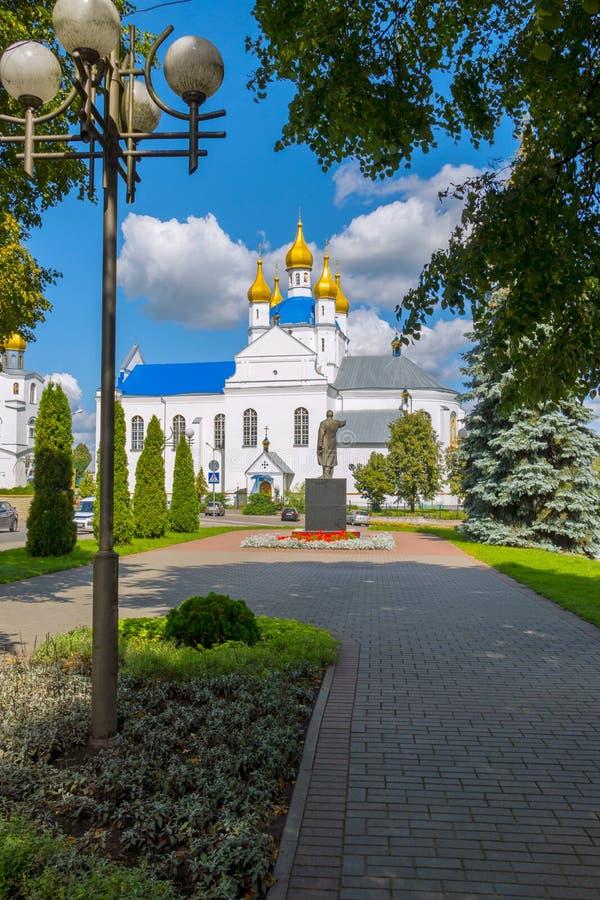 Памятник к руководителю на фоне большой красивой белой церков с золотыми куполами стоковые фото