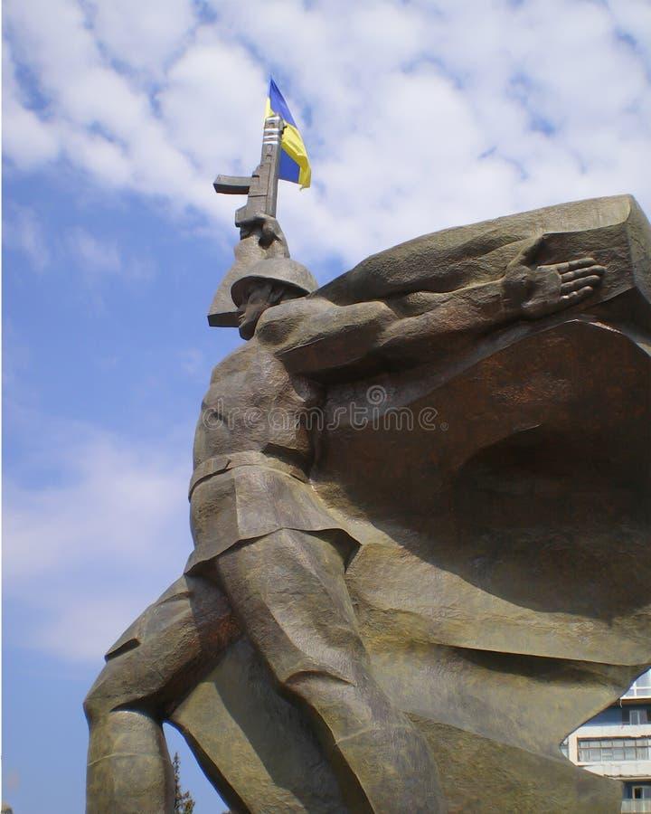 Памятник советскому солдату с украинским флагом связанным к пулемету стоковая фотография