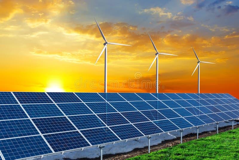 Панели солнечных батарей и ветротурбины на заходе солнца стоковое фото