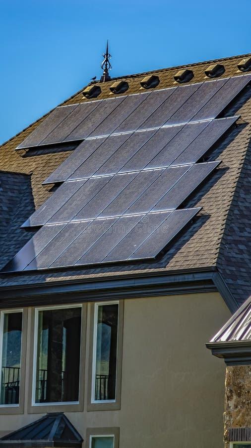 Панели солнечных батарей панорамы на темном - серая крыша с предпосылкой голубого неба на солнечный день стоковое фото rf