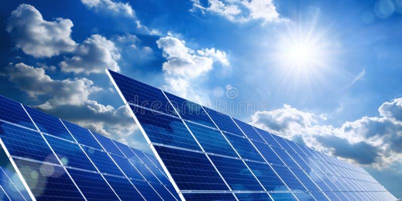 Панели солнечных батарей с голубым небом, солнцем и облаками стоковые фотографии rf