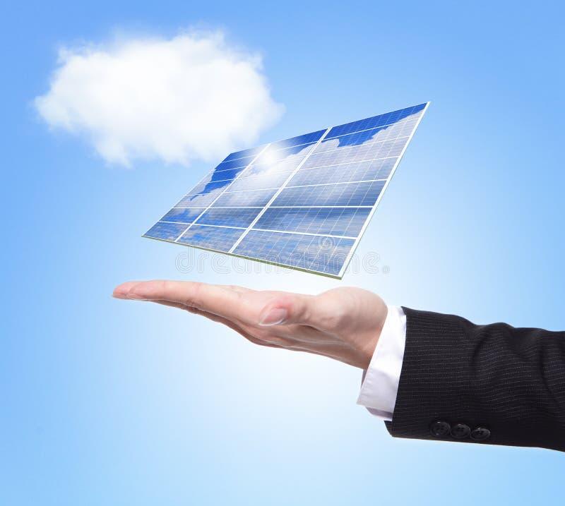 Панель солнечных батарей владением бизнесмена стоковые изображения