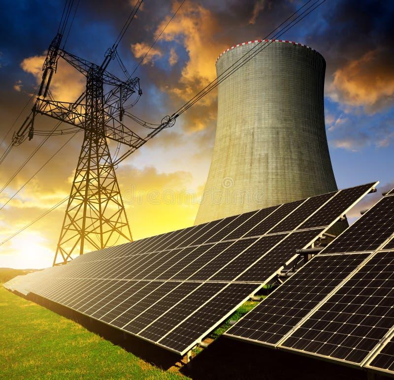 Панели солнечной энергии, атомная электростанция и опора электричества стоковая фотография rf