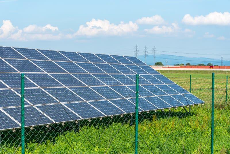 Панели солнечных батарей в поле с голубым небом производят возобновляющую энергию от солнца стоковое фото