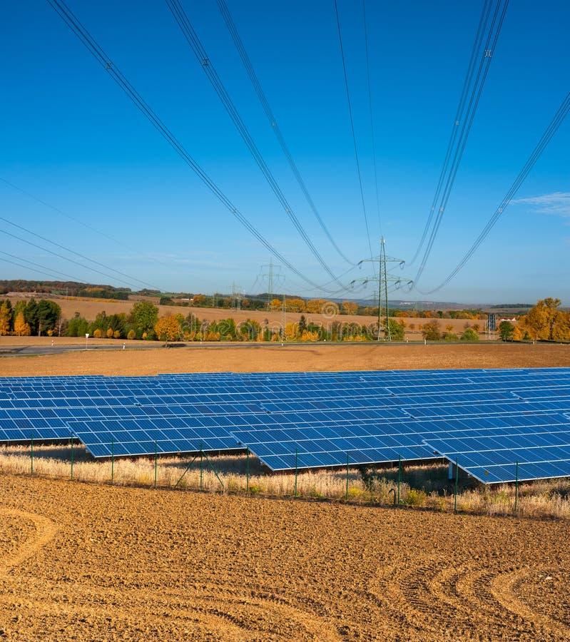 Панели солнечных батарей и линии электропередач стоковое изображение