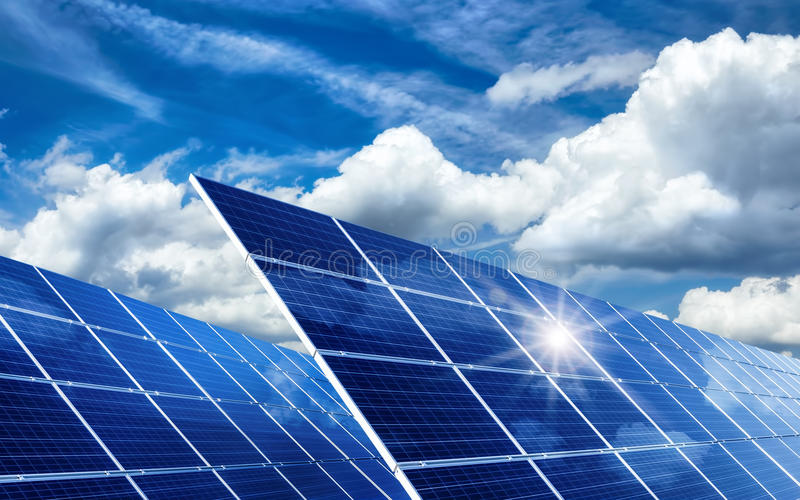 Панели солнечных батарей отражая солнце и облака стоковое фото