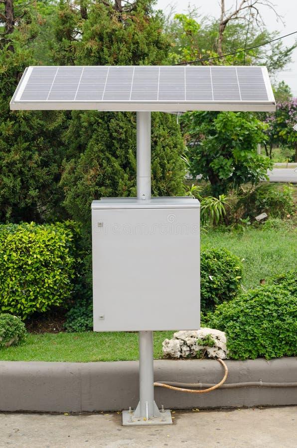 Панели солнечных батарей против, большие панель солнечных батарей и распределительные коробки стоковые изображения
