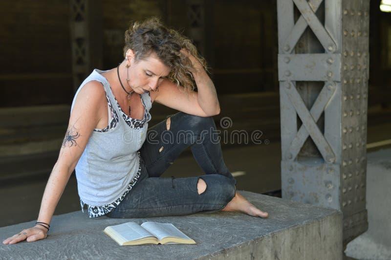 Панковская женщина читая библию стоковые фото