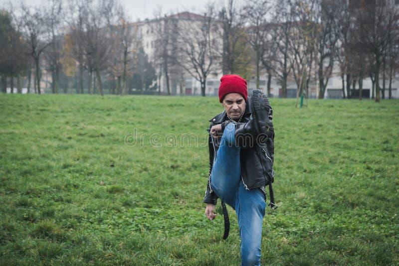 Панковский парень представляя в парке города стоковые фото
