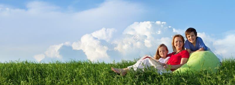 Панорама весны при семья сидя outdoors стоковые изображения rf
