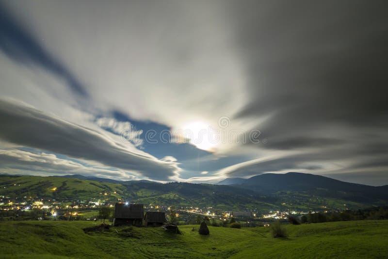 Панорама горы ночи лета Старые деревянные выдержанные хижины чабана на зеленой расчистке на пасмурной выравниваясь предпосылке не стоковая фотография