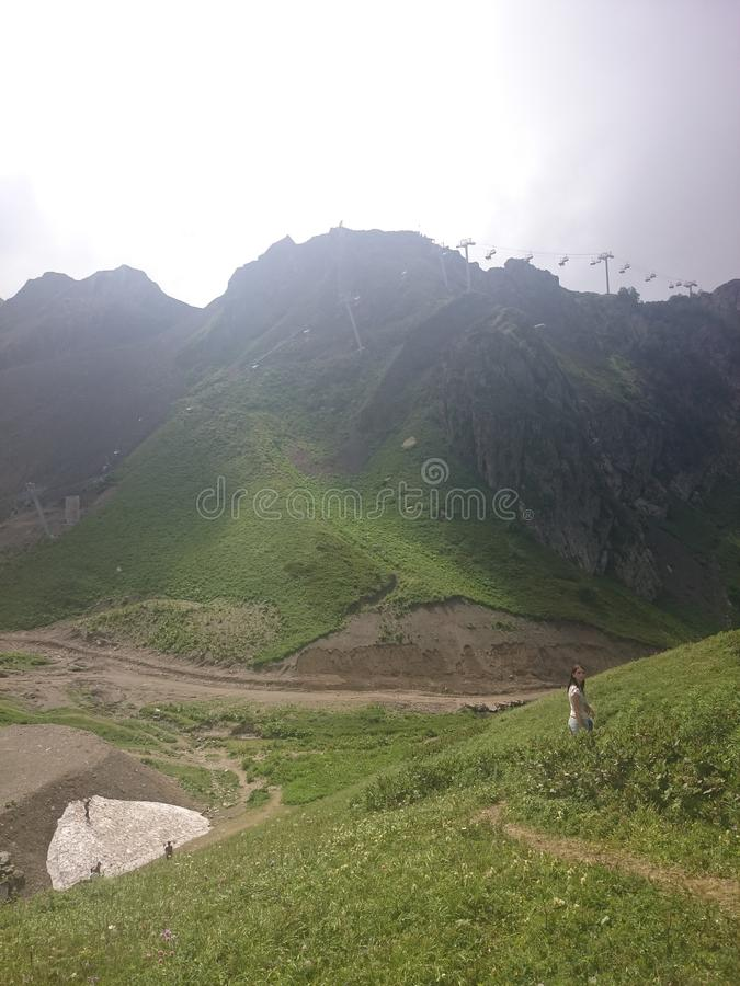 Панорама гор и гребня Aibga с облаками нижнего яруса Остатки снега и свежей зеленой травы на горах около стоковая фотография