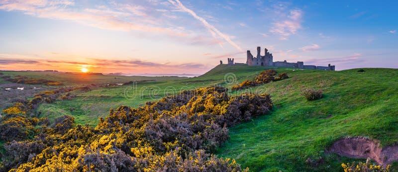 Панорама замка Dunstanburgh на заходе солнца стоковые фотографии rf
