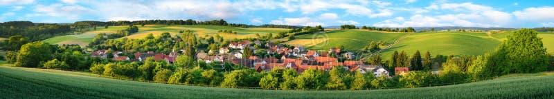 Панорама малой деревни окруженной зелеными холмами стоковое изображение rf
