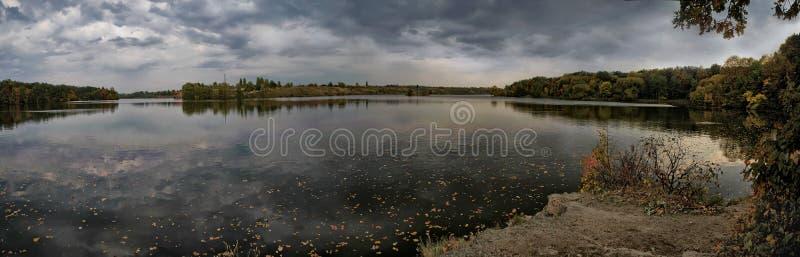 Панорамные взгляды реки с плавать желтые листья хмуро стоковые изображения