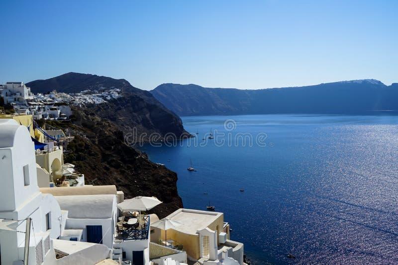 Панорамный взгляд голубого Эгейского моря, парусные судна и океан мочат отражение от деревни Oia с белым городским пейзажем здани стоковые фото
