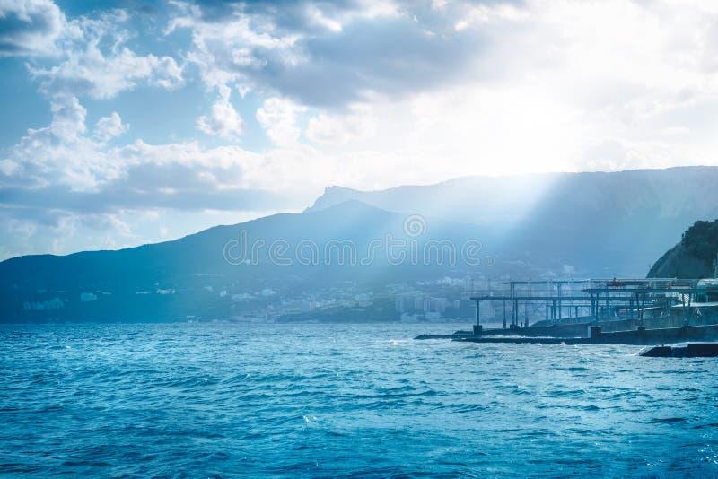 Панорамный взгляд моря вечера с пустыми пляжем & солнцем ярко светит в светя волнах Чёрное море, Ялта, Крым стоковое фото