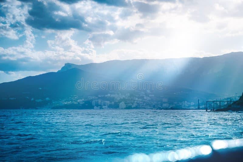 Панорамный взгляд моря вечера с пустыми пляжем & солнцем ярко светит в светя волнах Чёрное море, Ялта, Крым стоковые фотографии rf