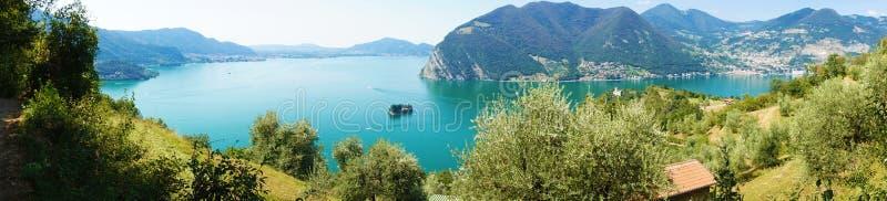 Панорамный взгляд озера горы с островом в середине Панорама от острова Monte Isola с озером Iseo итальянский ландшафт стоковые фото
