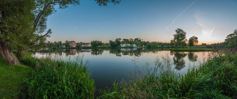 Панорамный взгляд от побережья через озеро в парке города к старому зданию Ландшафт лета вечера прибрежные тростники Ясное небо стоковое изображение
