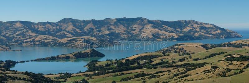 Панорамный взгляд Akaroa, полуострова банков, Крайстчёрча Новой Зеландии Фото принятое на ясный день ` s лета стоковое фото