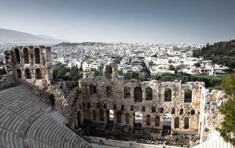 Панорамный вид белых зданий и Odeon театра камня Аттика Herodes под акрополем в Афина, Греции стоковое изображение