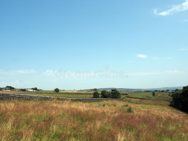 Панорамный вид длинной каменной стены между травой покрыл поля около головы blackshaw в Западном Йоркшире с далекими сельскими до стоковая фотография rf