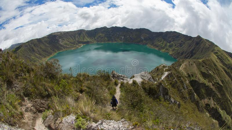 Панорамный вид изумрудно-зеленой лагуны внутри кратера вулкана Quilotoa стоковое фото