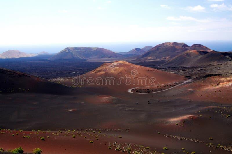 Панорамный вид над бесконечной сюрреалистической долиной на вулканических конусах и кратерах с запачканным горизонтом - Timanfaya стоковые изображения rf