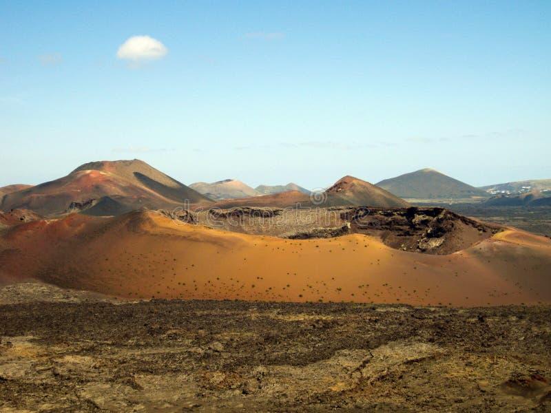 Панорамный вид над полем лавы на кратере и конусе красных вулканов в Timanfaya NP, Лансароте, Канарских островах стоковая фотография