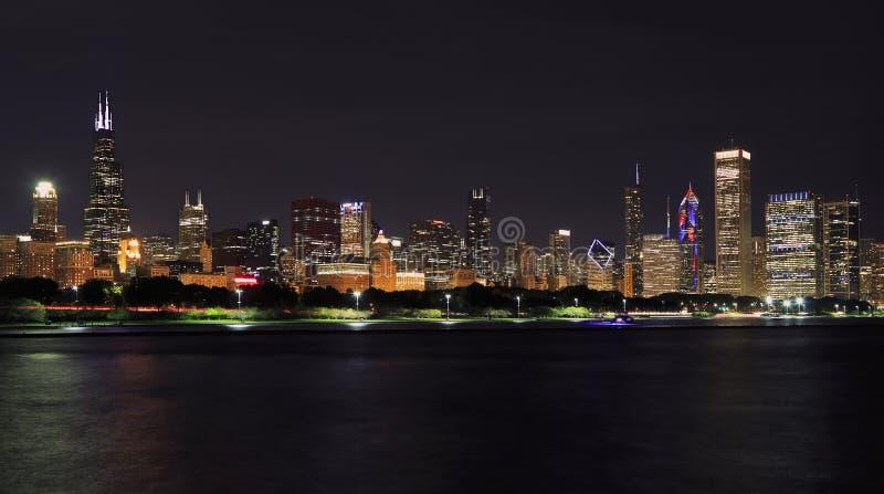 Панорамный вид на горизонт Чикаго ночью с озером Мичиган на переднем плане стоковые изображения