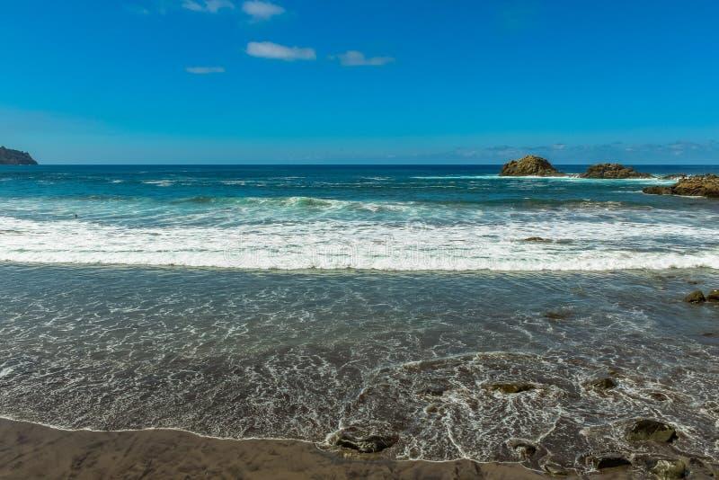 Панорамный вид пляжа Aimasiga с вулканической отработанной формовочной смесью и уединенными утесами вставляя из пены моря на севе стоковое фото