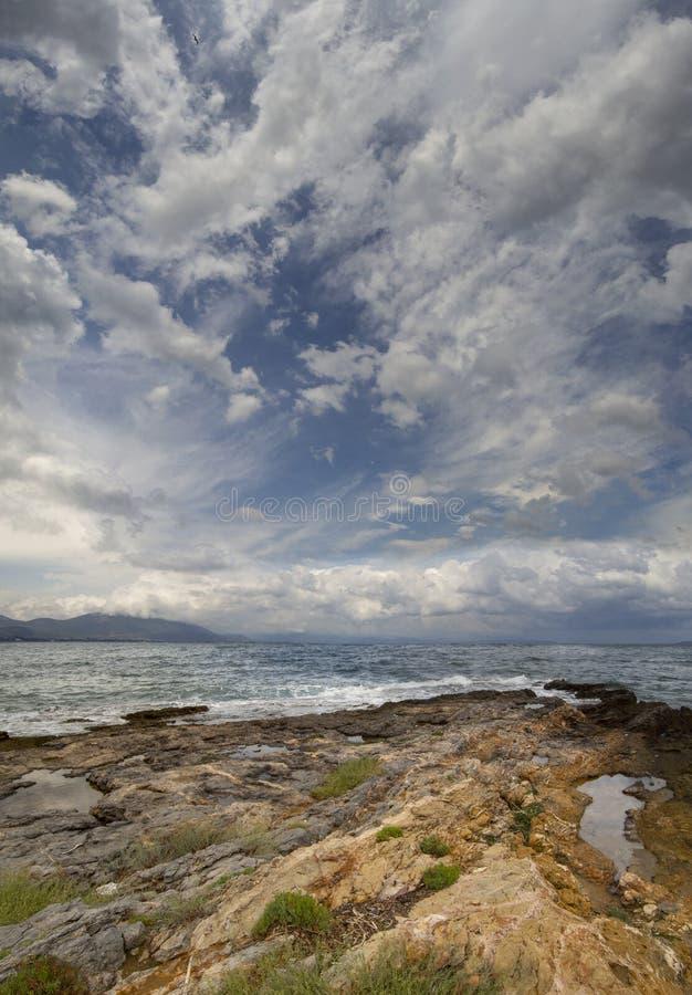 Панорамный вид сногсшибательных облаков шторма, волн и скалистого пляжа в Эгейском море на летний день на острове Evia, Gr стоковое фото rf