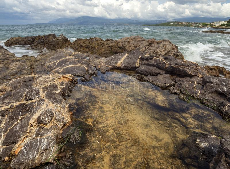 Панорамный вид сногсшибательных облаков шторма, волн и скалистого пляжа в Эгейском море на летний день на острове Evia, Gr стоковое фото