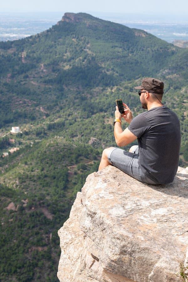 Панорамный вид туриста на горном пике стоковое изображение