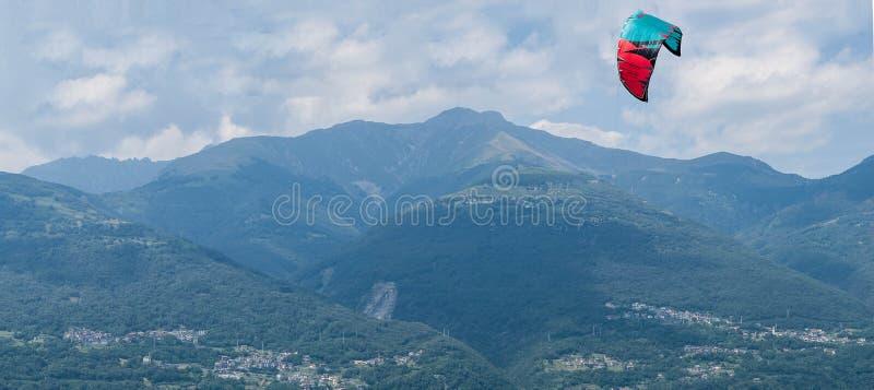 Панорамный вид kitesurfing парашюта на предпосылке гор горной вершины на яркий летний день Оборудование Kiteboarding против пасму стоковое изображение rf