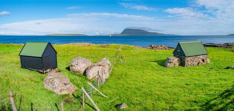 Панорамный вид seashore Фарерских островов с традиционными домами фермы стоковая фотография