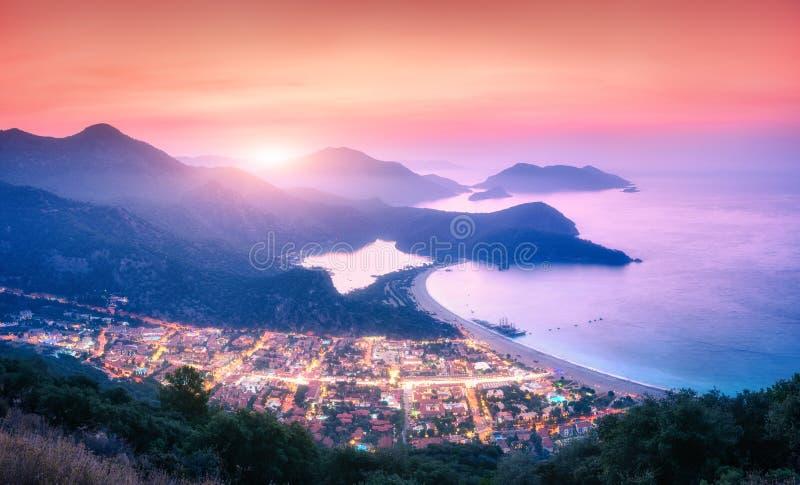 Панорамный ландшафт с голубой лагуной, морем, городом освещает, горы стоковая фотография rf