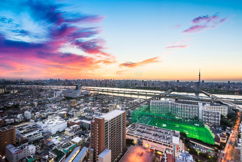 Панорамный современный вид с воздуха глаза птицы горизонта города под драматическим заревом захода солнца в токио, Японии стоковая фотография