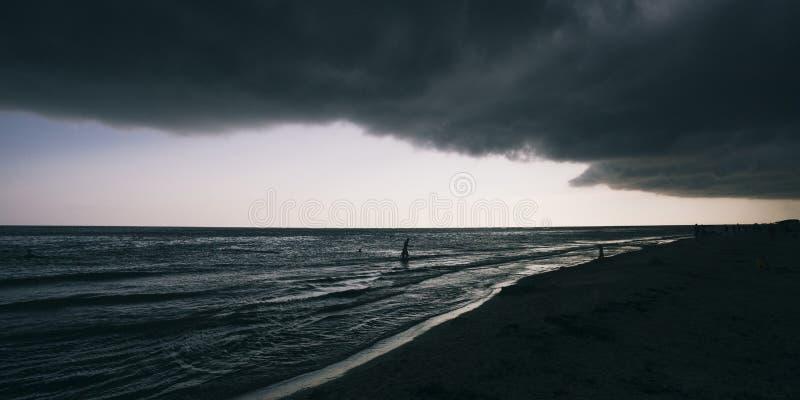 Панорамный широкоэкранный взгляд на темносиних море или океане с драматический тонизировать на заходе солнца Большие черные облак стоковое фото rf